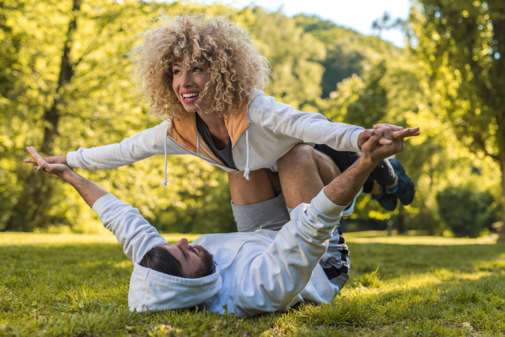 Couple exercising acroyoga in the park.