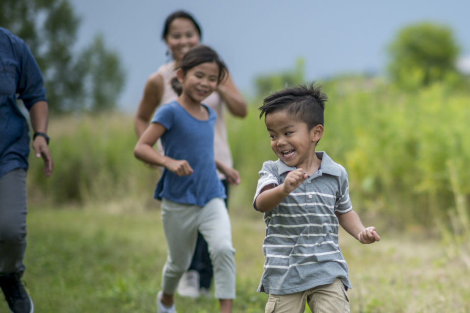 A young family is spending time together outside at the park. They are running through a grassy field.